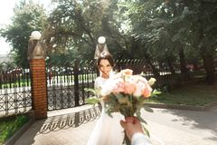 Beautiful young bride in stylish white dress, smiling meets her groom in the park stock photos
