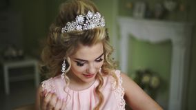 Beautiful Young Bride. Stylish Woman Fiancee with Bridal Hairstyle, Event Makeup and Jewelry. Girl straightens her hair with her hand. Close UP stock footage