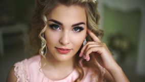 Beautiful Young Bride. Stylish Woman Fiancee with Bridal Hairstyle, Event Makeup and Jewelry. He looks up at the camera. stock video