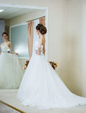 Beautiful young bride in wedding dress front of the mirror. Stock Photo