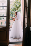 Beautiful young bride in wedding dress holding a cute bouquet standing on the balcony of vintage building Stock Photo