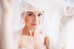 Beautiful young bride with wedding makeup and hairstyle in bedroom.Beautiful bride portrait with veil over her face. Closeup. Portrait of young gorgeous bride Stock Photos