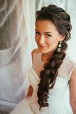 Beautiful young bride with wedding makeup and hairstyle in bedroom, newlywed woman final preparation for wedding. Happy Bride wait stock photo