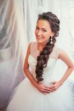 Beautiful young bride with wedding makeup and hairstyle in bedroom, newlywed woman final preparation for wedding. Happy Bride wait royalty free stock photo