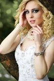 Beautiful young bride in white dress with bouquet near tree in summer green park Stock Photos