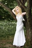 Beautiful young bride in white dress with bouquet near tree in summer green park Royalty Free Stock Image