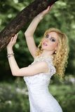 Beautiful young bride in white dress with bouquet near tree in summer green park Stock Photo