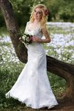 Beautiful young bride in white dress with bouquet near tree in summer green park Royalty Free Stock Photo