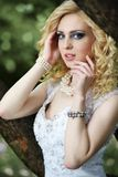 Beautiful young bride in white dress with bouquet near tree in summer green park Royalty Free Stock Images