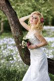 Beautiful young bride in white dress with bouquet near tree in summer green park Royalty Free Stock Photos