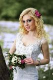 Beautiful young bride in white dress with bouquet in summer green park Royalty Free Stock Photography