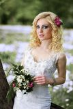 Beautiful young bride in white dress with bouquet in summer green park Royalty Free Stock Image