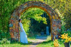 Beautiful and young bride in white dress and circlet of flowers posing in stone arch royalty free stock image