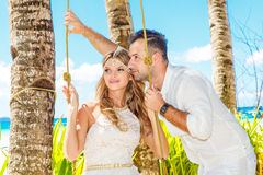 Beautiful young bride in a white dress and groom under a palm tr. Ee on a tropical beach. Summer vacation Stock Photos