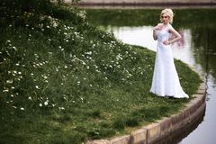 Beautiful young bride in white dress near lake in summer green park Stock Image