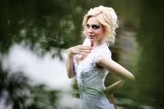 Beautiful young bride in white dress near lake in summer green park Stock Photos