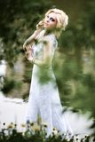 Beautiful young bride in white dress near lake in summer green park Royalty Free Stock Images