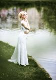Beautiful young bride in white dress near lake in summer green park Royalty Free Stock Photography
