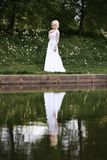 Beautiful young bride in white dress near lake in summer green park Stock Images