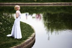 Beautiful young bride in white dress near lake in summer green park Royalty Free Stock Image