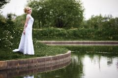 Beautiful young bride in white dress near lake in summer green park Royalty Free Stock Photo