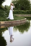 Beautiful young bride in white dress near lake in summer green park Stock Photo