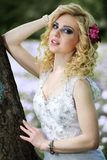 Beautiful young bride in white dress near tree in summer green park Stock Image
