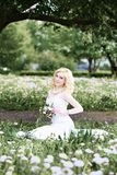Beautiful young bride in white dress sits field in summer green park Stock Photo