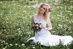 Beautiful young bride in white dress sits field in summer green park Stock Images