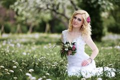 Beautiful young bride in white dress sits field in summer green park Stock Photography