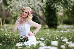 Beautiful young bride in white dress sits field in summer green park Royalty Free Stock Photography