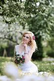 Beautiful young bride in white dress sits field in summer green park Royalty Free Stock Photos