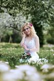 Beautiful young bride in white dress sits field in summer green park Royalty Free Stock Photo