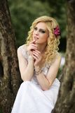 Beautiful young bride in white dress sits on tree in summer green park Stock Photo