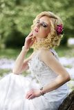 Beautiful young bride in white dress sits on tree in summer green park Stock Photography