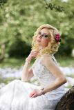 Beautiful young bride in white dress sits on tree in summer green park Stock Image