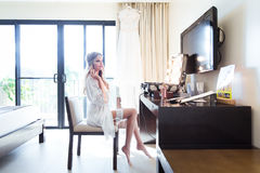 Beautiful young bride in a white dress sitting in hotel in front Royalty Free Stock Photo