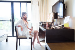 Beautiful young bride in a white dress sitting in hotel in front Stock Image