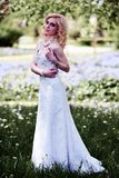 Beautiful young bride in white dress in summer green park Stock Photography