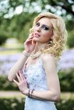 Beautiful young bride in white dress in summer green park Stock Photo