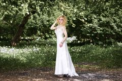 Beautiful young bride in white dress in summer green park Stock Photos