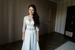 Beautiful young bride in white dress waiting for the groom indoors. Stock Image
