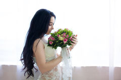 Beautiful young bride in a white dress with a wedding bouquet of Stock Photos
