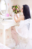 Beautiful young bride in a white dress with a wedding bouquet of Royalty Free Stock Photography