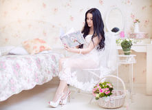 Beautiful young bride in a white dress with a wedding bouquet of Royalty Free Stock Image