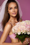 Beautiful young bride in white veil and pale pink lace lingerie with bouquet of peonies in hand Royalty Free Stock Photo