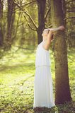 Beautiful young bride in white wedding dress leaning against tree outdoors Royalty Free Stock Photography