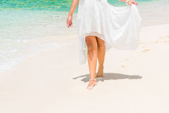 Beautiful young bride in a white wedding dress walking on a trop. Ical sandy beach. feet close-up Stock Photos