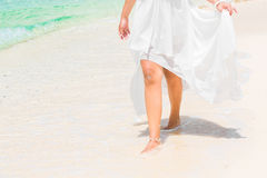 Beautiful young bride in a white wedding dress walking on a trop. Ical sandy beach. feet close-up Stock Images
