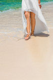 Beautiful young bride in a white wedding dress walking on a trop. Ical sandy beach. feet close-up Stock Photography